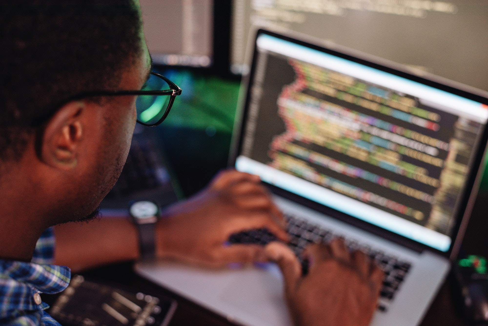 black male in front of computer screen coding mobile app web development computer programming